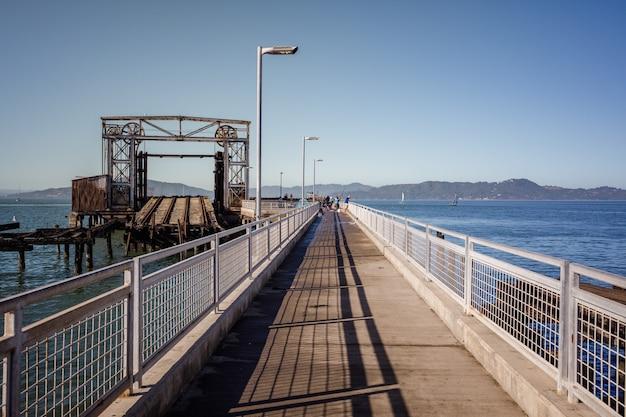 Bruine houten brug over de blauwe zee onder de blauwe hemel overdag
