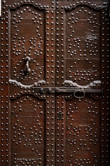 Bruine houten deuren met veel metalen klinknagels en houtsnijwerk met een lange bout en deurklopper