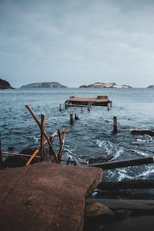 Bruine houten ladder op bruine rots dichtbij waterlichaam overdag