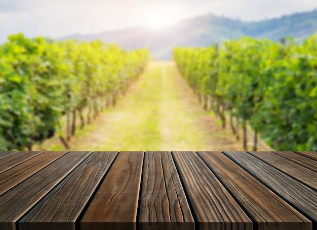 Bruine houten tafel in wijngaardlandschap met lege kopie ruimte op tafel voor productvertoning mockup.