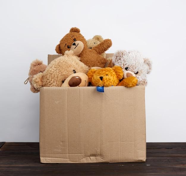 Bruine kartonnen doos gevuld met zacht speelgoed