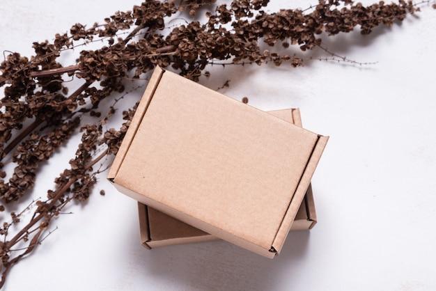 Bruine kartonnen kartonnen doos versierd met gedroogde tak mock up