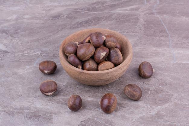 Bruine kastanjes in een houten beker op marmer.