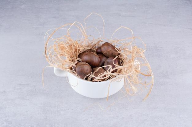 Bruine kastanjes in een rustieke versierde beker. hoge kwaliteit foto