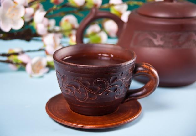 Bruine keramische theepot en kop met thee. de taksakura van de bloesemkers op de achtergrond. aziatische oosterse stijl.