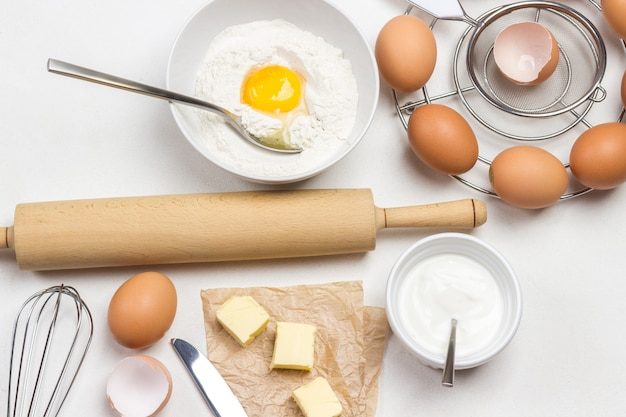 Bruine kippeneieren in kartonnen container, bloem, gebroken ei en lepel in kom op witte achtergrond