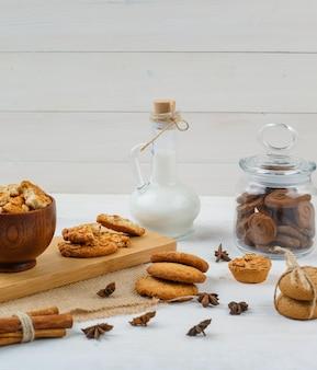 Bruine koekjes in een glazen pot met een kan melk, koekjes en kaneel
