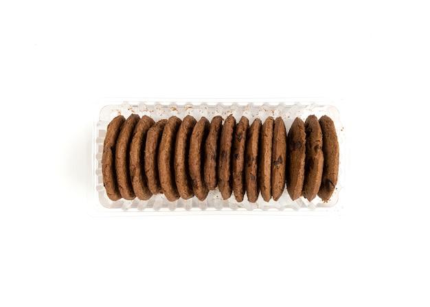 Bruine koekjes in een plastic container die op witte achtergrond wordt geïsoleerd. Premium Foto