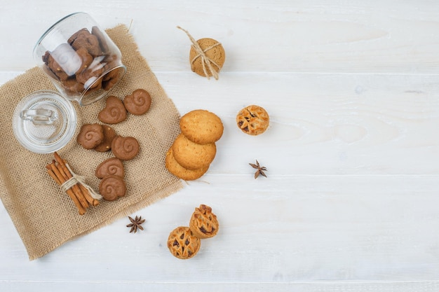 Bruine koekjes in een pot, kaneel in een placemat met witte koekjes