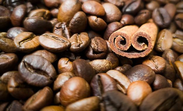 Bruine koffiebonen en kaneelstokje achtergrond.