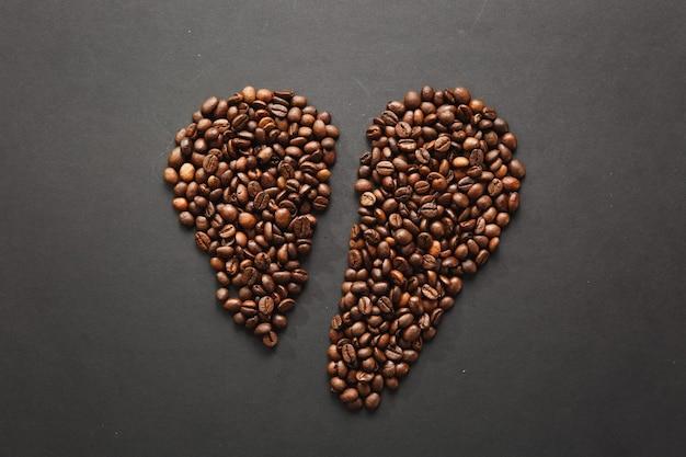 Bruine koffiebonen in de vorm van een gebroken hart geïsoleerd op een zwarte textuurachtergrond voor ontwerp. saint valentine's day-kaart op 14 februari, vakantieconcept.
