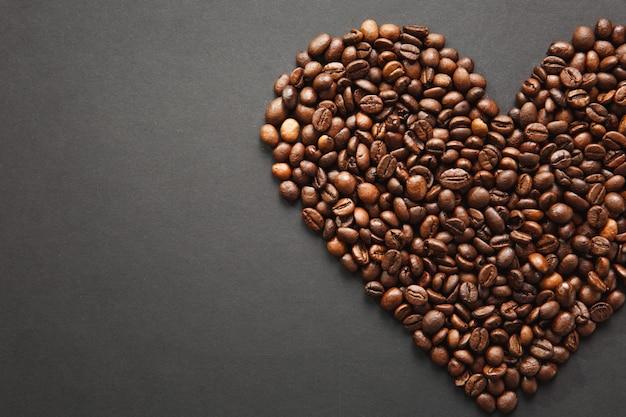 Bruine koffiebonen in de vorm van een hart geïsoleerd op een zwarte textuurachtergrond voor ontwerp, een deel of de helft. saint valentine's day-kaart op 14 februari, vakantieconcept.