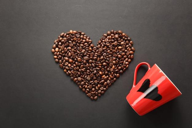 Bruine koffiebonen in de vorm van een hart met rode kop voor thee met harten geïsoleerd op een zwarte textuurachtergrond voor ontwerp. saint valentine's day-kaart op 14 februari, vakantieconcept.