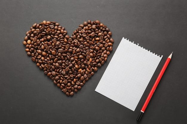 Bruine koffiebonen in de vorm van hart geïsoleerd op zwarte textuur achtergrond voor design. saint valentine's day-kaart op 14 februari, vakantieconcept. notebook, wit blanco vel, rood potlood. plaats voor tekst