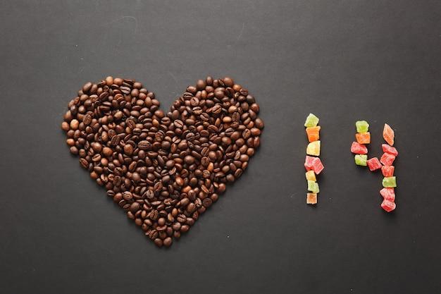 Bruine koffiebonen in de vorm van hart geïsoleerd op zwarte textuur achtergrond voor design. saint valentine's day-kaart op 14 februari, vakantieconcept. nummer 14 van gekleurde vierkante gekonfijte vruchten of schil.
