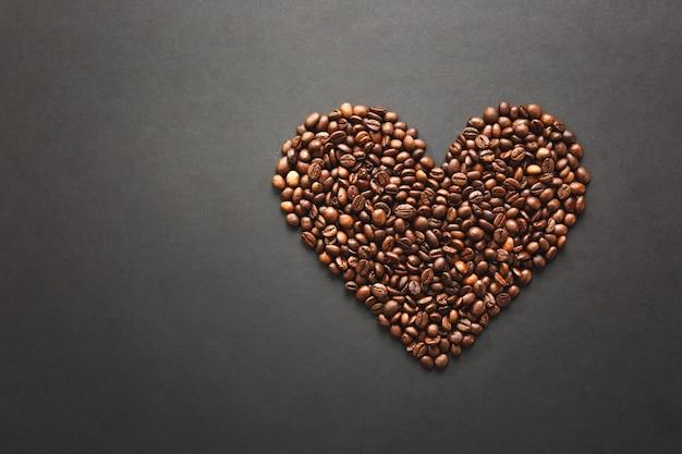 Bruine koffiebonen in de vorm van hart geïsoleerd op zwarte textuur achtergrond voor design. saint valentine's day-kaart op 14 februari, vakantieconcept.