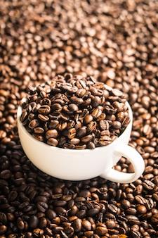 Bruine koffiebonen in witte kop