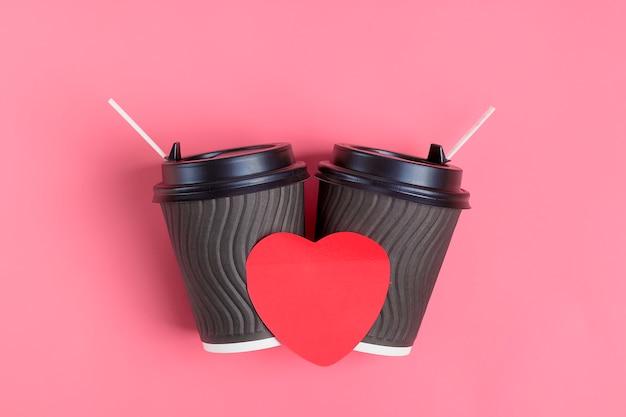 Bruine koffiekoppen, rode hartvormige sticker op roze achtergrond. fijne valentijnsdag