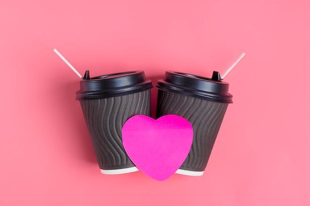 Bruine koffiekoppen, rode hartvormige sticker op roze achtergrond. happy valentijnsdag flat lag