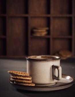 Bruine kop koffie en traditionele nederlandse stroopwafels. voedseloppervlakte met exemplaarruimte