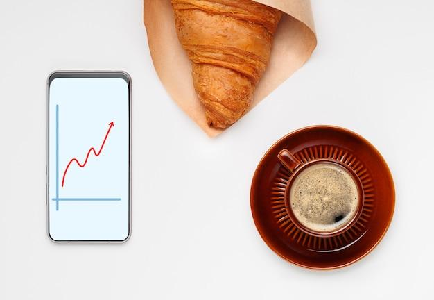 Bruine kop zwarte koffie met schotel, croissant en telefoon