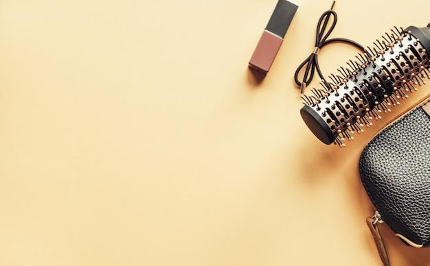 Bruine kosmetische zak en haarborstel en lippenstift op pastelkleur gele achtergrond.
