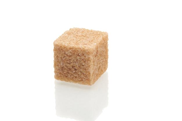 Bruine kubus van rietsuiker geïsoleerd op een witte achtergrond. close-up bekijken.