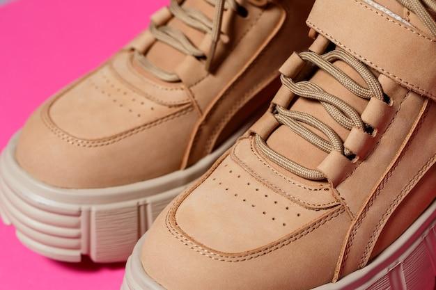 Bruine leren damesschoenen met hoge zolen op een roze achtergrond. mode schoeisel