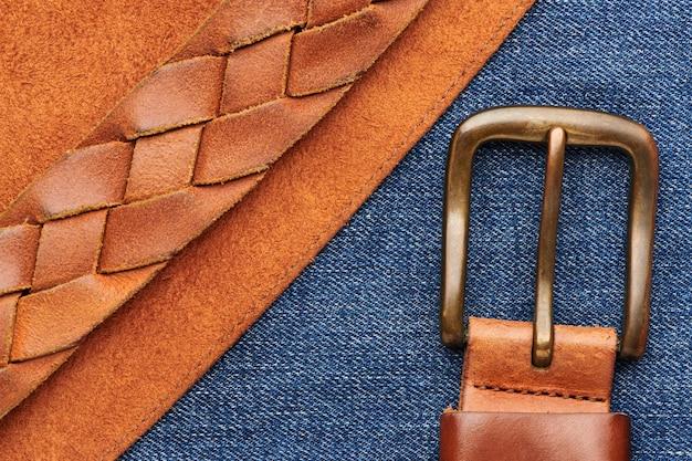 Bruine leren riem met bronzen gesp op zeemleer en jeans