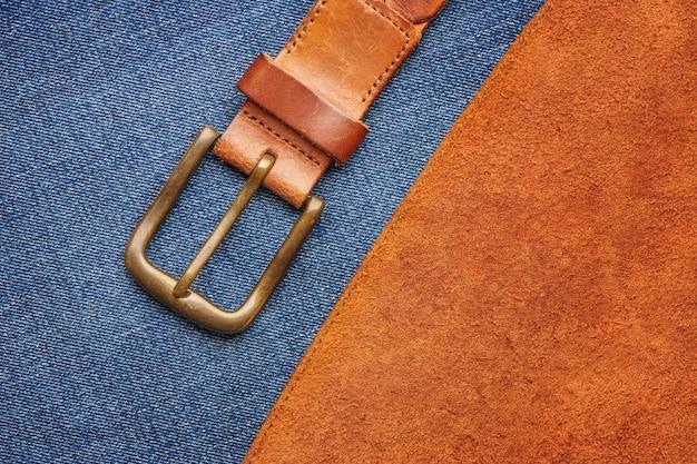 Bruine leren riem met bronzen gesp op zeemleer en jeans Premium Foto