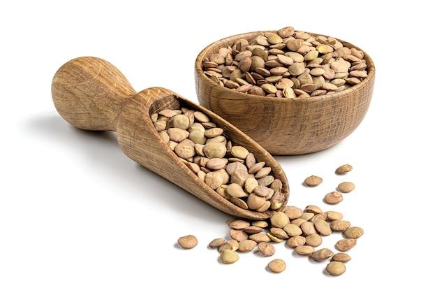 Bruine linzenbonen in een houten kom en scoop geïsoleerd op een witte achtergrond. natuurlijk vegetarisch voedselingrediënt.