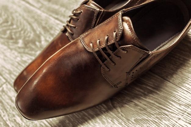 Bruine mannelijke schoenen op houten vloer