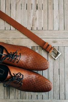 Bruine mans schoenen met veters op een houten ondergrond