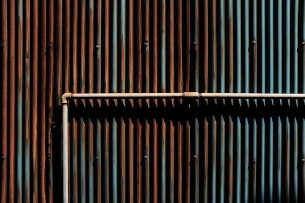 Bruine metalen buis op bruine en blauwe roestige palen