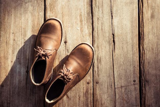Bruine modieuze laarzen op houten achtergrond, retro kleur