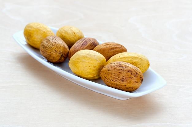 Bruine noten die op een rij op een schotel liggen