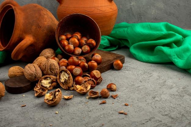 Bruine noten in bruine pot geheel en geschild samen met groen weefsel en mooie kannen op een grijs bureau