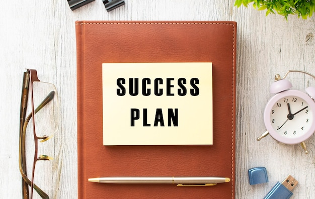 Bruine notitieboekjesticker met het opschrift succesplan