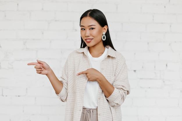 Bruine ogen vrouw in stijlvol vest abs beige broek glimlacht, kijkt naar de camera en wijst op de plaats voor tekst op witte bakstenen muur