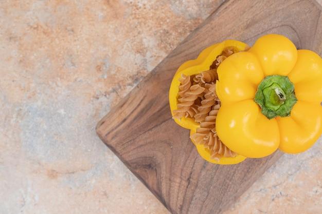 Bruine ongekookte spiraalvormige macaroni met peper op een houten bord
