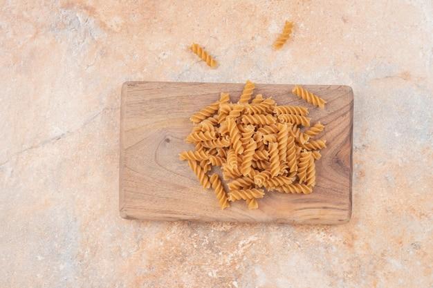 Bruine ongekookte spiraalvormige macaroni op een houten bord.