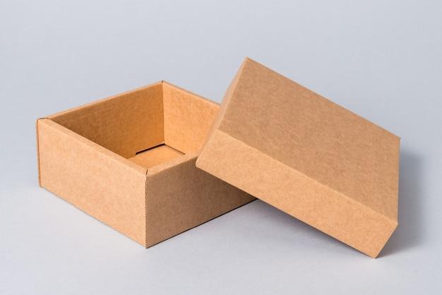 Bruine openned kartonnen geschenkdoos met deksel op grijze achtergrond
