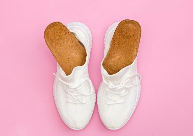 Bruine orthopedische inlegzolen voor schoenen. witte sneakers op een roze achtergrond.