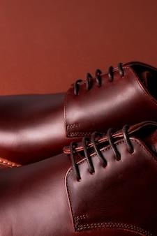 Bruine oxford schoenen op rood. detailopname.