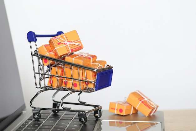 Bruine pakketdoos en model miniatuurboodschappenwagentje op computertoetsenbord voor online het winkelen