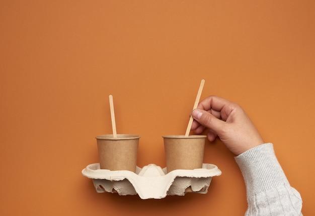 Bruine papieren bekers in een papierlade en een hand met een houten stok op een bruine achtergrond, geen plastic, geen afval