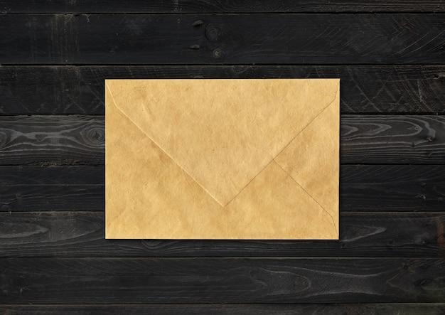 Bruine papieren envelop geïsoleerd op zwarte houten achtergrond