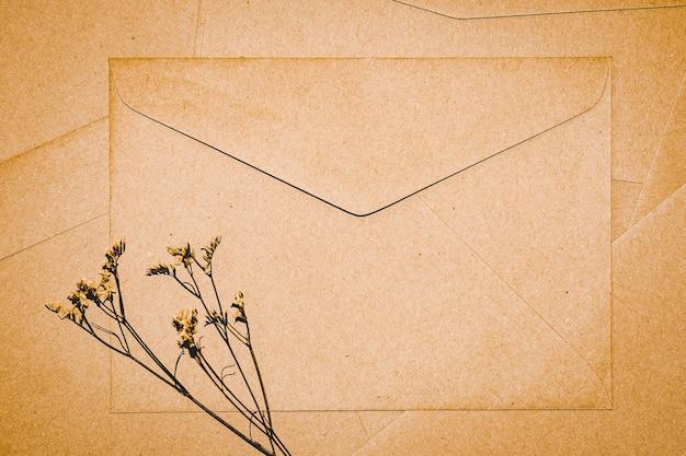 Bruine papieren envelop met limonium droge bloem. close-up van craft envelop. platliggend minimalisme.