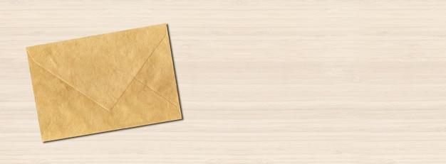 Bruine papieren envelop op witte houten achtergrond