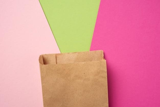 Bruine papieren wegwerpvoedselzak op een roze achtergrond